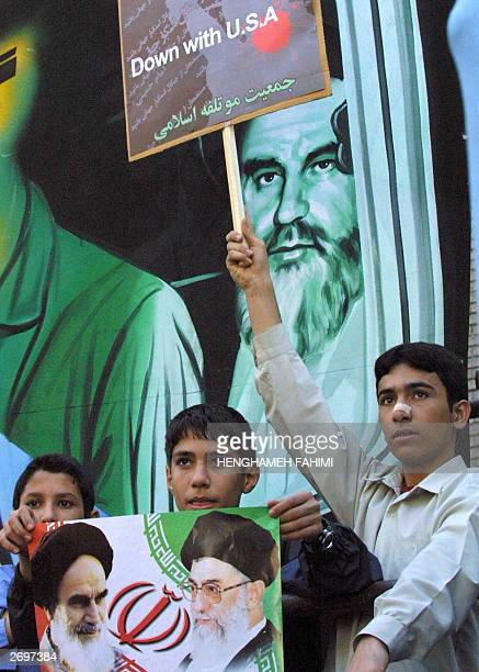 An Iranian student holds up a poster of the late Iranian leader and founder of the Islamic Republic Ruhollah Khomeini and Iranian supreme leader Ali...
