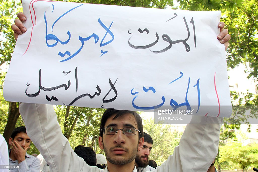An Iranian student holds up a sign that reads, 'death to American, death to Israel', as he attends an anti-Israeli demonstration in front of the United Nations offices in Tehran, on May 6,2013, to condemn Israeli air strikes on targets near the Syrian capital Damascus. Israeli raids on Syrian targets at the weekend killed at least 15 soldiers, a watchdog said, as UN chief Ban Ki-moon led calls for restraint to prevent the war spilling over borders. AFP PHOTO/ATTA KENARE