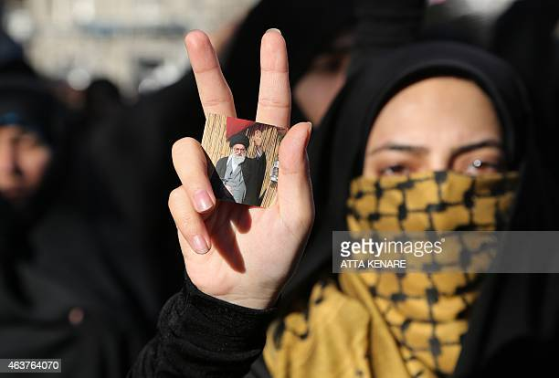 An Iranian student shows flashes the sign of victory holding a portrait of Iran's Supreme Leader Ayatollah Ali Khamenei during a demonstration on...