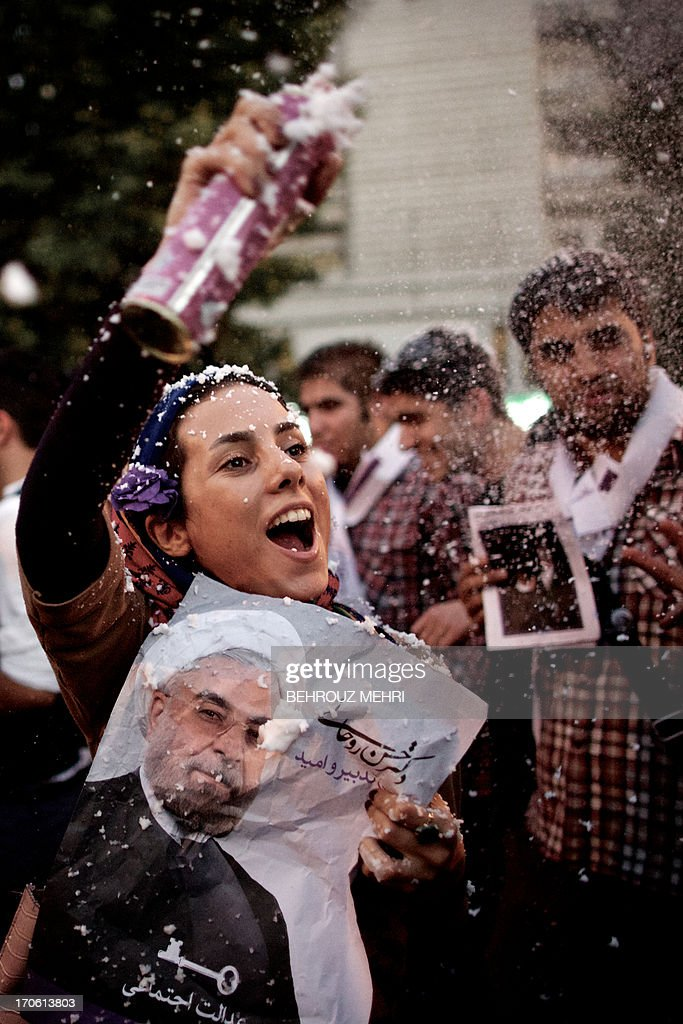 An Iranian supporter of moderate presidential candidate Hassan Rowhani hold his portrait as she sprays artificial snow to celebrate his victory in Valiasr street in Tehran on June 15, 2013. AFP PHOTO/BEHROUZ MEHRI