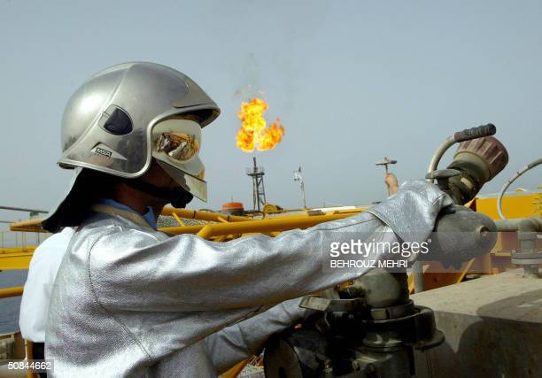 An Iranian technician works at the Balal offshore oil platform in the Gulf waters in the Gulf on the edge of Qatar's territorial waters 16 May 2004...