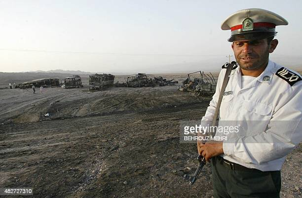 An Iranian traffic policeman stands guard by the wreckage of burnt buses trucks and gasoline tanker at the Nosrat Abad police post 115km west of the...