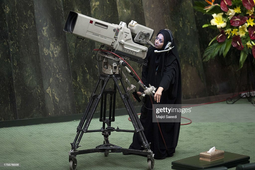 An Iranian TV camera woman films President Hassan Rowhani as he is sworn in at parliament, on August 4, 2013 in Tehran, Iran. As he swore his oath of office Rouhani called on the West to abandon the 'language of sanctions' in its dealings with the country. He promised to represent all Iranians, advance women's rights and dedicate himself to serving the people with moderation.