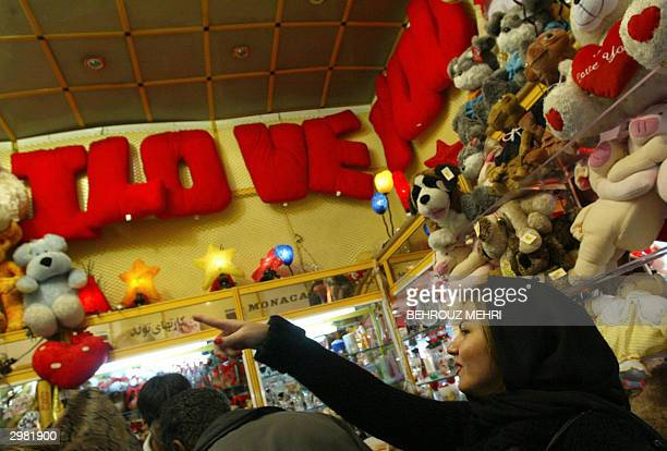 An Iranian woman buys a gift on Valentine's day in Tehran 14 February 2004 Valentine's Day named after a Christian patron saint for lovers has gained...