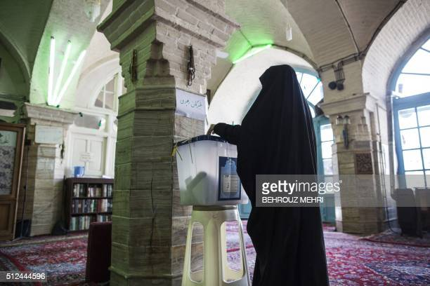 An Iranian woman casts her ballot for the Assembly of Experts election at a polling station in the holy city of Qom 130kms south of the capital...