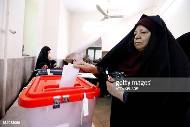 An Iranian woman casts her ballot for the presidential elections at a polling station in southern Tehran on May 19 2017 / AFP PHOTO / ATTA KENARE