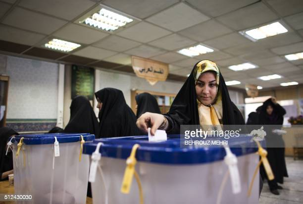An Iranian woman casts her ballot to vote for both parliamentary elections and Assembly of Experts at a polling station at Massoumeh shrine in the...