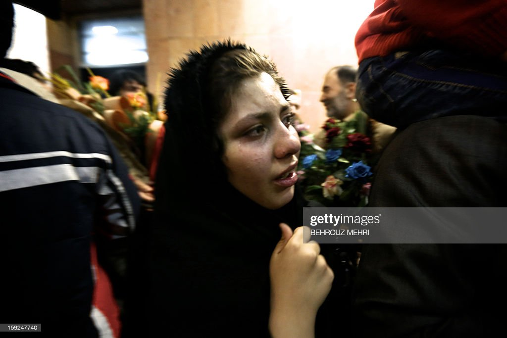 An Iranian woman cries as she looks for her father Reza Sohrabi who has been held hostage, alongside 48 other Iranians, by Syrian rebels since early August 2012, at Tehran's Mehrabad airport on January 10, 2013. The rebels agreed to swap the 48 Iranians, described by the Islamic republic as pilgrims but by the rebels and Washington as members of Iran's elite Revolutionary Guards, for more than 2,000 detainees held by the Syrian regime. AFP PHOTO / BEHROUZ MEHRI