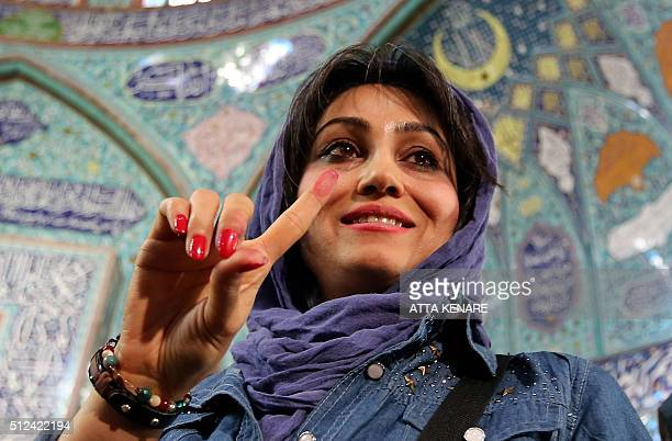 An Iranian woman displays her inkstained finger after casting her ballot for both parliamentary elections and the Assembly of Experts at a polling...