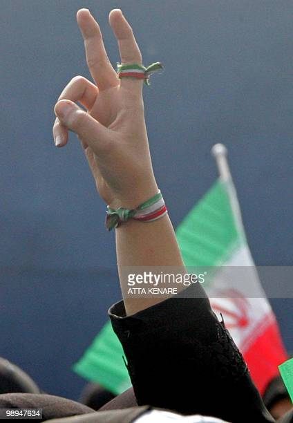 An Iranian woman flashes the Vsign of victory with the colours of the national flag around her finger and wrist during a mass rally held in Azadi...