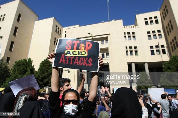 An Iranian woman hiding her face not to be identified raises up a placard during a protest in front of the judiciary building on October 22 2014 in...