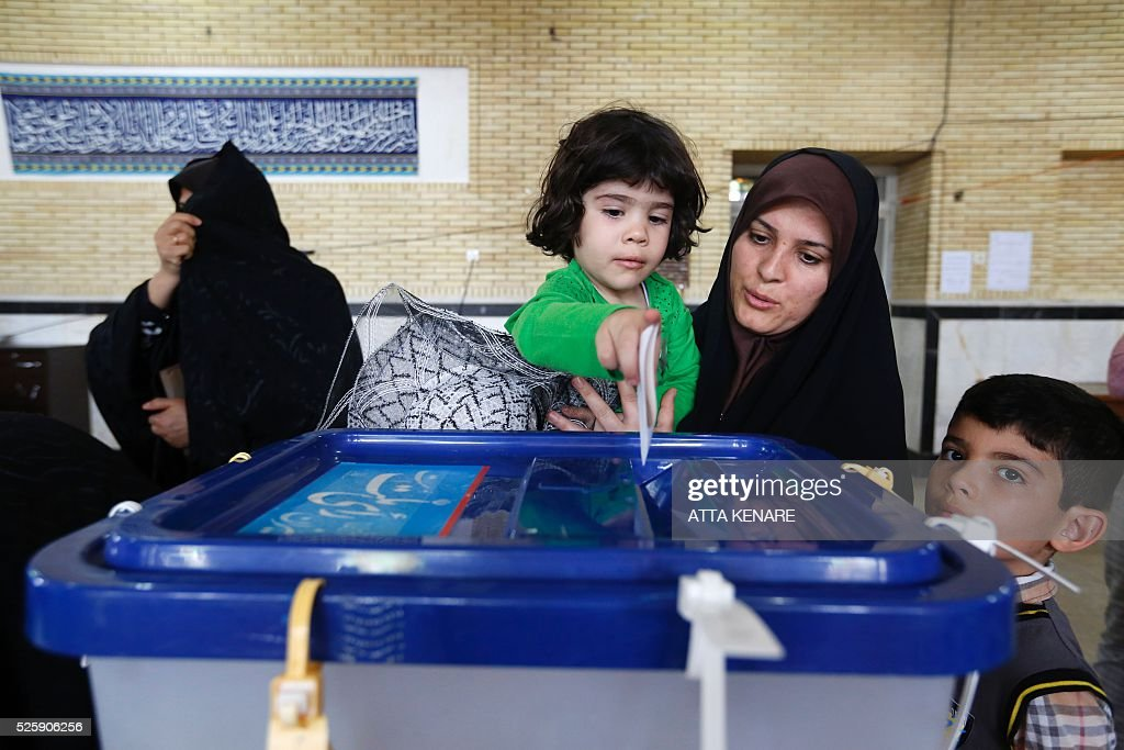 An Iranian woman holds a child to help her cast her ballot as she votes in the second round of parliamentary elections at a polling station in the town of Robat Karim, some 40 kms southwest of the capital Tehran, on April 29, 2016. Iranians started voting in second round elections for almost a quarter of parliament's seats, the latest political showdown between reformists and conservatives seeking to influence the country's future. Polling stations opened at 8:00 am (0330 GMT) for the ballot which is taking place in 21 provinces, but not Tehran, because no candidate in 68 constituencies managed to win 25 percent of votes cast in initial voting on February 26. Reformists who backed moderate President Hassan Rouhani made big gains in the first round following Iran's implementation of a nuclear deal with world powers, which lifted sanctions blamed for long hobbling the economy. Conservative MPs, including vehement opponents of the West who openly criticised the landmark agreement that reined in Iran's atomic programme, lost dozens of seats and were wiped out in Tehran where reformists won all 30 places in parliament. / AFP / ATTA
