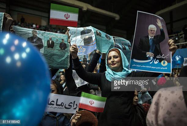 An Iranian woman holds a national flag and a poster bearing a portrait of reformists' number one candidate Mohammad Reza Aref during a reformists...