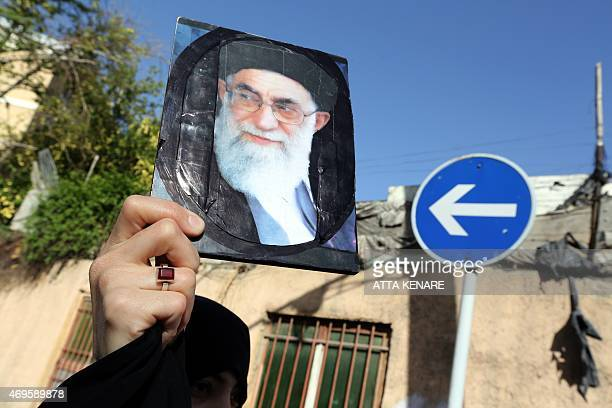 An Iranian woman holds a portrait of Iran's supreme leader Ayatollah Ali Khamenei duringa demonstration against the Saudiled coalitions Operation...
