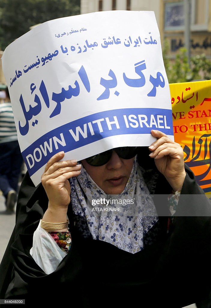 An Iranian woman holds an anti-Israeli slogan during a parade marking al-Quds (Jerusalem) Day in Tehran on July 01, 2016. Tens of thousands joined pro-Palestinian rallies in Tehran, as the annual Quds Day protests take on broader meaning for a region mired in bitter disputes and war. KENARE