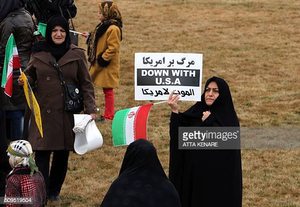 An Iranian woman holds an antiUS slogan during celebrations in Tehran's Azadi Square to mark the 37th anniversary of the Islamic revolution on...