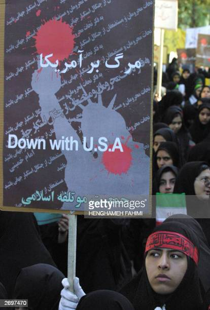 An Iranian woman holds up a placard in front of the former US embassy in Tehran 04 November 2003 Some 10000 Iranian hardliners gathered outside the...