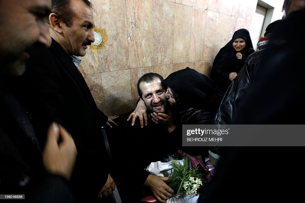 An Iranian woman kisses Ahmad Arayan (C) who has been held hostage, alongside 48 other Iranians, by Syrian rebels since early August 2012, after arriving at Tehran's Mehrabad airport on January 10, 2013. The rebels agreed to swap the 48 Iranians, described by the Islamic republic as pilgrims but by the rebels and Washington as members of Iran's elite Revolutionary Guards, for more than 2,000 detainees held by the Syrian regime. AFP PHOTO / BEHROUZ MEHRI