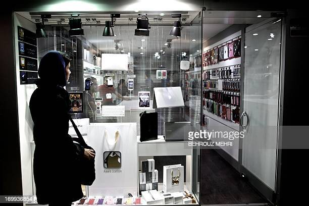 An Iranian woman looks at the windowshop of a computer store selling Apple products at a mall in northern Tehran on June 1 2013 The United States...