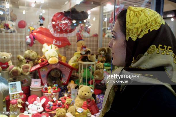 An Iranian woman looks at Valentine's Day gifts in Tehran 14 February 2002 Young Iranians have been for a few days on a Valentine's buying mania with...