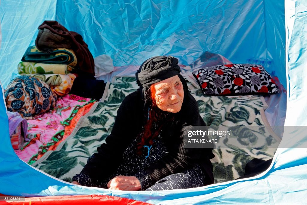 An Iranian woman looks out a tent where she is camped, near damaged buildings in the town of Sarpol-e Zahab in the western Kermanshah province near the border with Iraq, on November 14, 2017, following a 7.3-magnitude earthquake that left hundreds killed and thousands homeless two days before. /