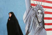 An Iranian woman passes by an anti US mural during a demonstration outside the US Embassy to mark the 25th anniversary of the seizure of the US...