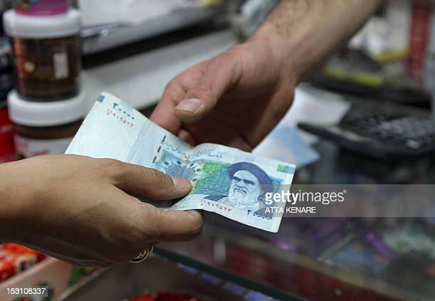 An Iranian woman pays a 20000 rial banknote bearing a portrait of Iran's late founder of islamic Republic Ayatollah Ruhollah Khomeini to a grocer in...