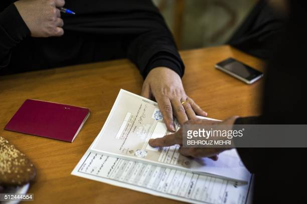 An Iranian woman presses her inkedfinger on a registering paper during the parliamentary and Assembly of Experts elections at a polling station at...
