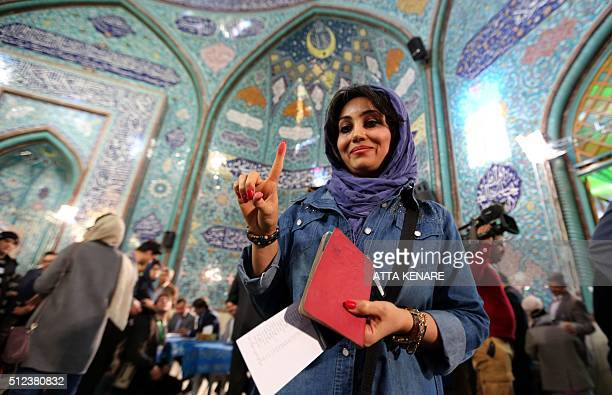 An Iranian woman shows her inked finger after casting her ballot at a polling station in Tehran on February 26 2016 Iranians began voting across the...