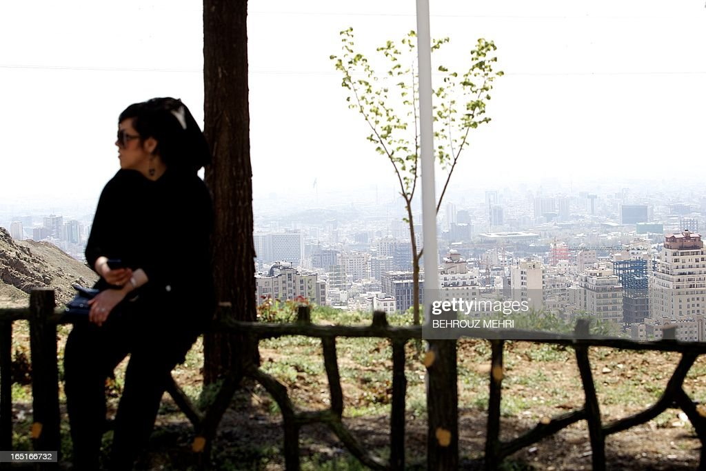 An Iranian woman sits on a fence overlooking a view of Tehran during their Noruz vacation from the foot of Tochal mountain in northern Tehran on April 1, 2013. Noruz, the new year according to the Persian solar calendar is a Zoroastrian tradition, still celebrated by Iranians even after Islam.