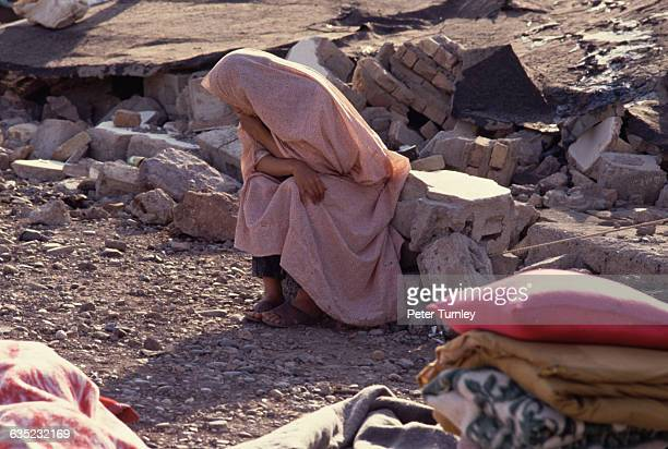 An Iranian woman sits on a pile of rubble in what used to be her town before a severe earthquake leveled it Casualty estimates have reached as high...