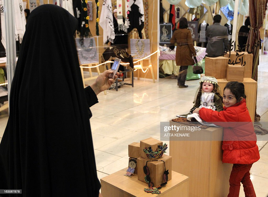 An Iranian woman takes a uses her mobile phone to take a picture of her daughter during their visit to the Second Fadjr International Fashion and Clothing Festival 2013, in the Iranian capital Tehran on March 3, 2013. The exhibition showcases conservative fashion for women and children, most of which is designed in Iran.