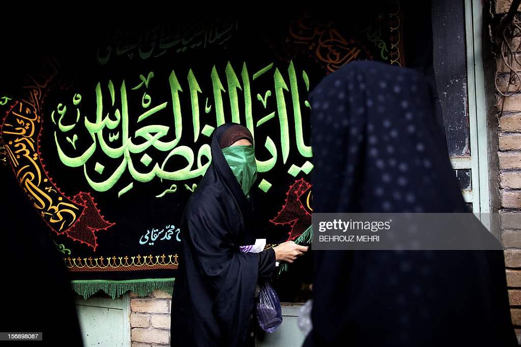 An Iranian woman touches a religious banner during the 'Chehel Manbar' (Forty Pulpits) ritual a day before Ashura, in the city of Khorramabad, 470 kilometres southwest of Tehran on November 24, 2012. Traditionally, Iranian women of Khorramabad walk barefoot to light candles in 40 designated places in the city centre on the eve of the Ashura, which marks the seventh century slaying of the grandson of Prophet Mohammed, Imam Hussein.