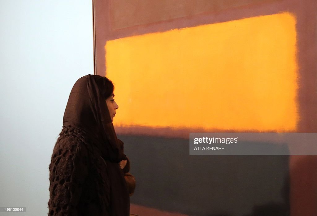 An Iranian woman walks by a painting titled 'Sienna Orange black on Dark Brown' by American artist Mark Rothko during the opening ceremony of an...