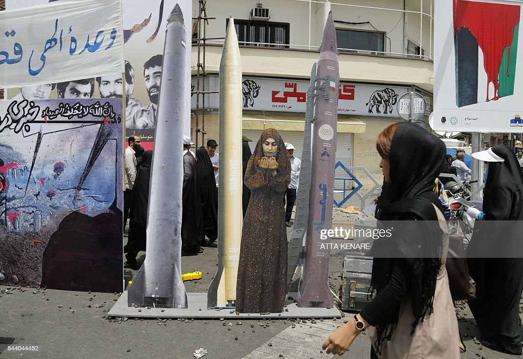 An Iranian woman walks past a cardboard cutout of a woman praying amidst rockets during a parade marking al-Quds (Jerusalem) Day in Tehran on July 01, 2016. Tens of thousands joined pro-Palestinian rallies in Tehran, as the annual Quds Day protests take on broader meaning for a region mired in bitter disputes and war. KENARE