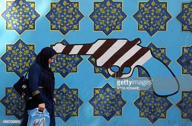 An Iranian woman walks past a mural depicting a revolver bearing the colours of the US national flag and spread on the wall of the former US embassy...