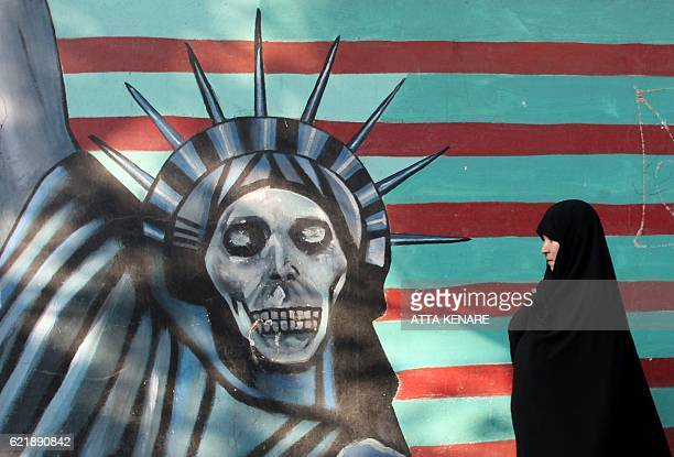 An Iranian woman walks past a mural on the wall of the former US embassy in the Iranian capital Tehran on November 9 2016 Iran's President Hassan...