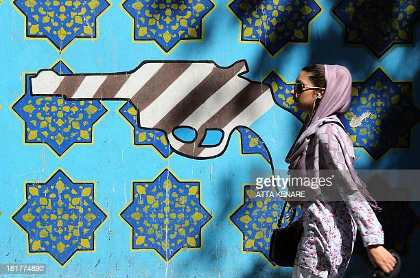 An Iranian woman walks past a mural showing a gun painted with an interpretation of the American flag on the wall of the former US embassy in Tehran...
