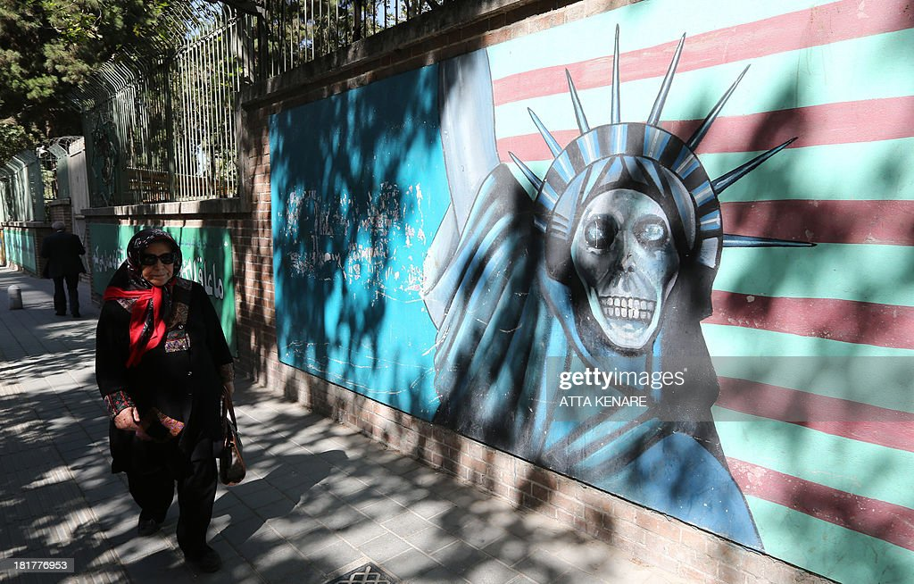 An Iranian woman walks past a mural showing an interpretation of the Statue of Liberty bearing the face of a skull on the wall of the former US embassy in Tehran on September 25, 2013. Leaders from Iran and the United States have not met since the 1979 Islamic Revolution brought often open hostility to their contacts, particularly over Iran's contested nuclear program.