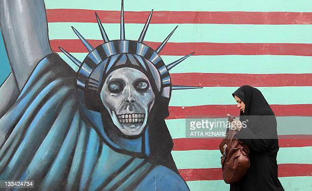 An Iranian woman walks past an antiUS mural painted on the wall of the former US embassy in Tehran on November 19 2011 The United States said Iran...