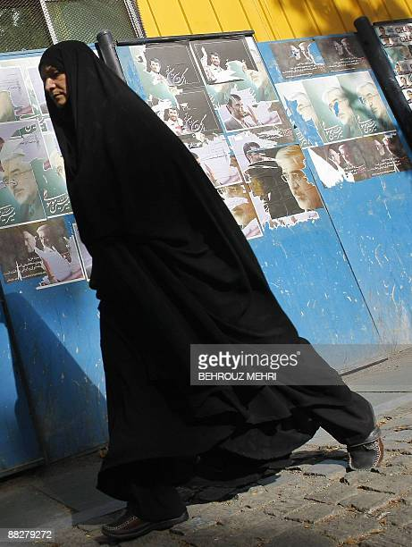 An Iranian woman walks past campaign posters of presidential candidates Mir Hossein Mousavi and Mahmoud Ahmadinejad in downtown Tehran on June 7 2009...
