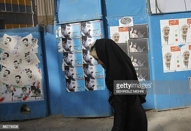 An Iranian woman walks past campaign posters of presidential candidates Mir Hossein Mousavi Mohsen Rezai and Mahmoud Ahmadinejad in downtown Tehran...
