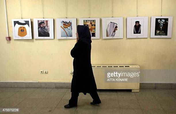 An Iranian woman walks past cartoons displayed during an exhibition as part of the Daesh International Cartoon and Caricature Contest on May 31 2015...
