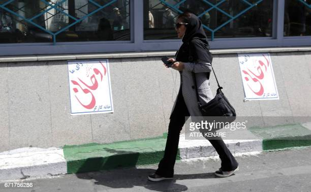 An Iranian woman walks past election posters of President Hassan Rouhani who is running for the presidential elections in Tehran on April 23 2017 /...