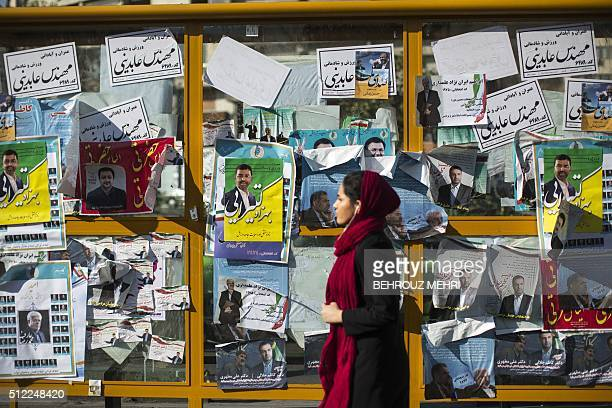 An Iranian woman walks past electoral posters for upcoming parliamentary elections in downtown Tehran on February 25 2016 / AFP / BEHROUZ MEHRI