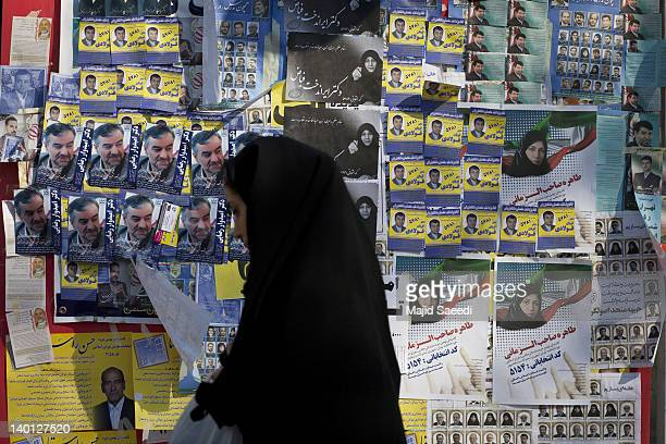 An Iranian woman walks past electoral posters of candidates for the upcoming parliamentary elections on February 28 2012 inTehran Iran Campaigning...