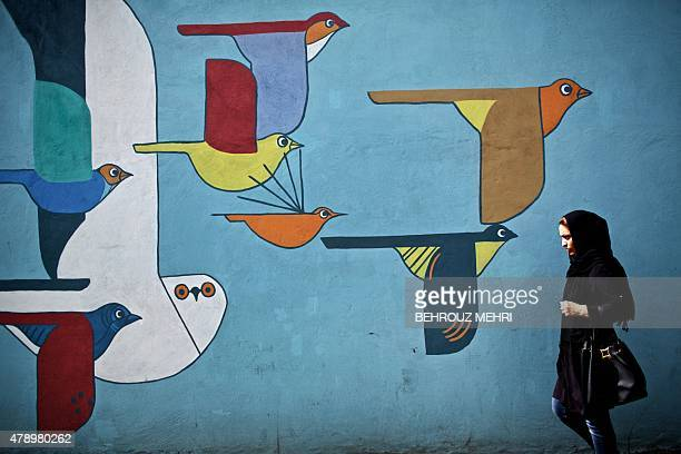 An Iranian woman walks past graffiti in a southwestern street of Tehran on June 29 2015 Despite agreeing the outlines of a nuclear agreement on April...