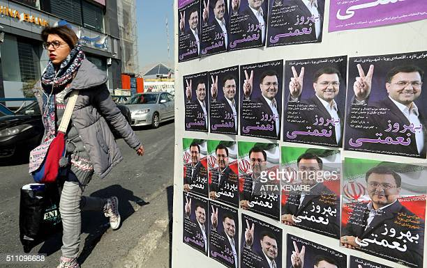 An Iranian woman walks past posters depicting portraits of Behrouz Nemati a candidate for the upcoming parliamentary elections in downtown Tehran on...