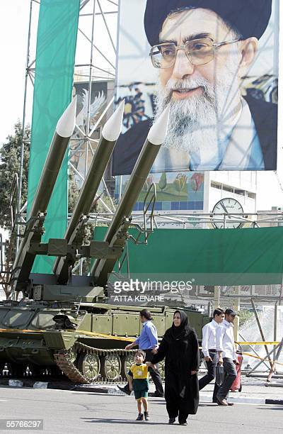 An Iranian woman walks past Russianmade Sam6 surfacetoair missiles are seen in front of a portrait of Iran's Supreme Leader Ayatollah Ali Khamenei at...