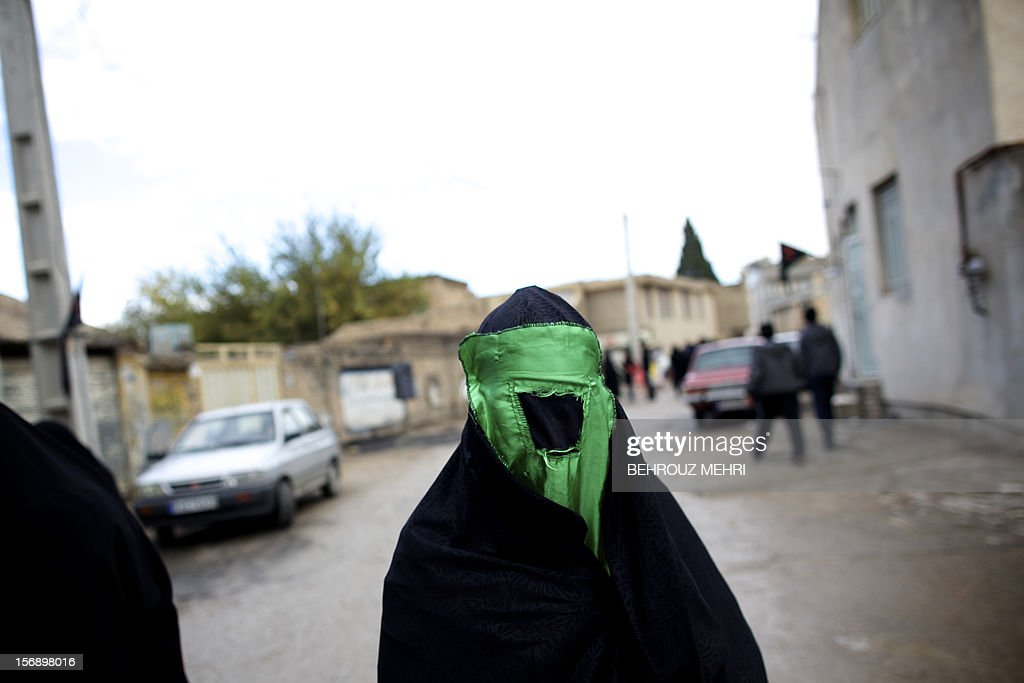 An Iranian woman wearing the Niqab walks in the street, as she lights candles, during the 'Chehel Manbar' (Forty Pulpits) ritual a day before Ashura, in the city of Khorramabad, 470 kilometres southwest of Tehran on November 24, 2012. Traditionally, Iranian women of Khorramabad walk barefoot to light candles in 40 designated places in the center of city on the eve of the Ashura, which marks the seventh century slaying of the grandson of Prophet Mohammed, Imam Hussein.